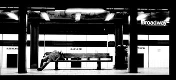 Rest in the new york metro. Photo taken in the subway of New York at night, the photo portrays a person sleeping on a bench in a moment of calm in what is Stock Photos