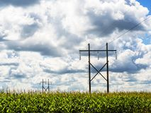Landscape of electric pylons. Photo taken in the summer of 2016, Drummondville, Quebec, Canada. The sky was cloudy and the pylons were in a cornfield stock photo