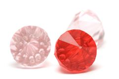 Three fake diamonds. A photo taken on three plastic molded fake diamonds against a white background. One is ruby red while the other two is light pink in color Royalty Free Stock Photo