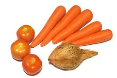 Three red tomatoes, five carrots and a coconut against a white backdrop Royalty Free Stock Photo