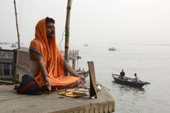 a sadhu seated on a ghat by the river, wearing a saffron robe, varanasi, uttar pradesh, india.