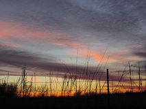 Winter Sunset Sky Behind Barbed Wire Fence Sihouette with Pink Purple Orange Clouds Stock Photos