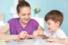 Photo of talented diligent small boy draws with great desire picture, uses colourful marker, cheerful mother helps to choose color royalty free stock photo