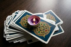 Photo of tarot card. Photo cards for fortune telling or playing. Tarot cards on a wooden background. With a burning candle Stock Images