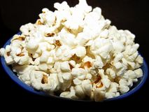 Salty popcorn in a blue bowl stock photos