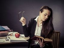Teacher sitting at her messy desk reading. Photo of a teacher in her 30`s sitting at a messy desk in front of a large blackboard reading a book Royalty Free Stock Photos