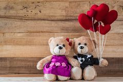 Teddy bear holding heart-shaped balloon. A photo of teddy bear holding heart-shaped balloon with wood board texture Royalty Free Stock Photos