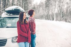 Teenagers in Christmas sweaters walking in snow in winter stock photo