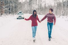 Teenagers in Christmas sweaters walking in snow in winter royalty free stock images