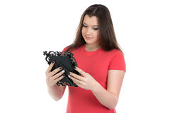 Photo of teenage girl looking at photo frame. On white background Stock Photos