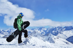 Photo on a theme of extreme sports, winter sports, snowboarding. Professional snowboarder standing with snowboard in the mountains. Beautiful mountain landscape stock photos