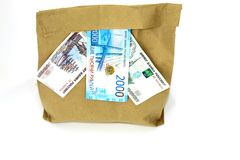 Money on a paper bag. White background. In the photo there are several objects: money from three bills five hundred rubles, one thousand rubles, two thousand stock image