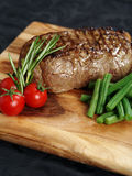 Steak dinner. Photo of a thick sirloin steak dinner with rosemary, cherry tomatoes and green beans on a wooden board Royalty Free Stock Photo