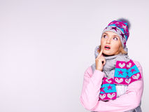 Photo of a thinking girl in winter clothes looking up Stock Images