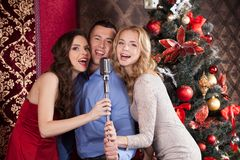 Photo of three frienda singing at party. Two beautiful happy girls holding mic stand Royalty Free Stock Photo