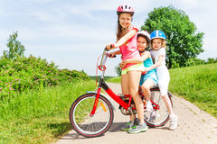 Photo of three girls sitting on a bicycle Royalty Free Stock Photos