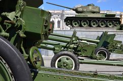Photo of three guns of the Soviet Union of the Second World War against the background of the green tank T-3. 4 Royalty Free Stock Photos