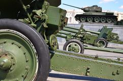 Photo of three guns of the Soviet Union of the Second World War against the background of the green tank T-3. 4 Stock Image