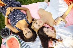 Photo of three happy girls lying on green grass and smiling. Stock Photography