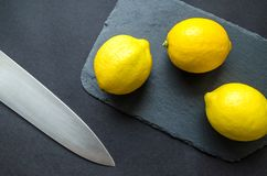 Photo of Three Lemons on Chopping Board Near Knife Royalty Free Stock Photos
