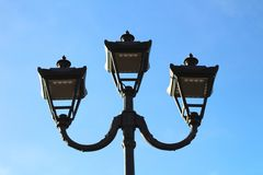 photo of three modern metal LED lamps in vintage style on a single post against a blue sky royalty free stock images