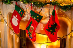 Photo of three red christmas socks hanging on burning fireplace Stock Images