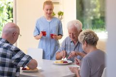 Seniors during dinner. Photo of three seniors eating during dinner time and young nurse with juice in glasses stock photography