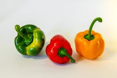 Three isolated fresh colorful peppers royalty free stock photos