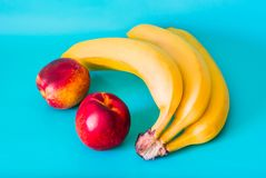 Three unpeeled ripe bananas and two beautiful, appetizing nectarines lie on a greenish-blue background stock photos