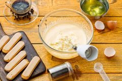 Photo of tiramis cooking, cups with whisk. Cookies, cheese on wooden table stock photo