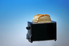 Photo of Toaster with White Bread. Toaster with White Bread on Blue Background stock photo