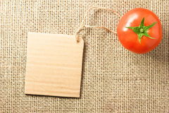 Tomato vegetable and price tag on sacking background texture Royalty Free Stock Image