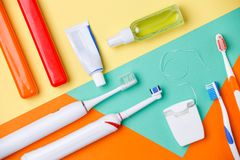 Photo of toothbrushes, tubes of pastes, floss. On orange, green and yellow background stock image