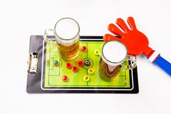 Photo on top of two mugs of beer, table football, ratchet toy. On white table royalty free stock image