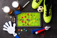 Photo on top of two mugs of foam beer, table football, ball, football boots, pipe, rattle toy. On black table royalty free stock photos