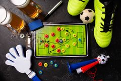 Photo on top of two mugs of foam beer, table football, ball, football boots, pipe, rattle toy. On black table stock images