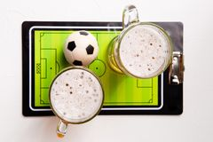 Photo on top of two mugs of frothy beer, table football, ball. On white table stock photo