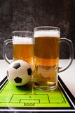 Photo on top of two mugs of frothy beer, table football, ball. On white table royalty free stock photography