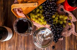 Photo on top of wine glasses, grapes of green and black, wooden basket, cloth. On wooden table Stock Photos