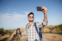 Photo of tourist man with walking sticks photographing himself on mountain hill royalty free stock photography