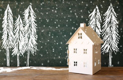 Photo of toy house in front of chalkboard with winter concept drawings Stock Photography