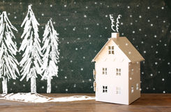 Photo of toy house in front of chalkboard with winter concept drawings Royalty Free Stock Photos