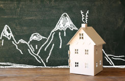 Photo of toy house in front of chalkboard with winter concept mountain drawings Stock Photo
