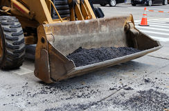Photo tractor scoop at work on road pavement. Tractor scoop at work on road pavement Royalty Free Stock Photo
