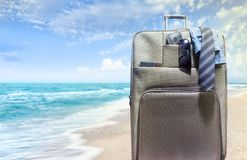 Travel suitcase on sea shore beach. stock images