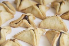 Traditional purim triangular pastry stuffed with figs. Photo of triangular pastry stuffed with figs, ears of Haman - Ozney Haman - hamantaschen, on a white Royalty Free Stock Image