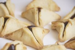 Traditional purim triangular pastry stuffed with figs. Photo of triangular pastry stuffed with figs, ears of Haman - Ozney Haman - hamantaschen, on a white Stock Photography