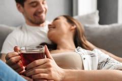 Photo trouble des couples gais se trouvant sur le sofa dans l'appartement, tandis que wom Photos libres de droits