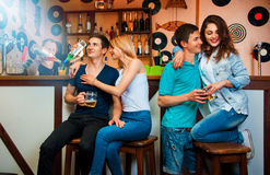 Photo of twins with their girlfriend at bar and barman cooking c Stock Images