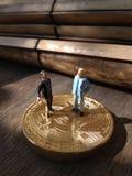 Photo two businessman mini figure toys, chit chat about bitcoin. Photo photo two businessman mini figure toys, chit chat about bitcoin stock photo